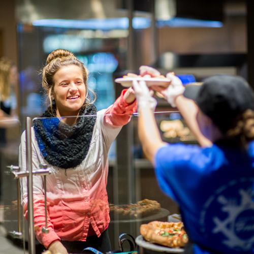 Market student receiving a piece of pizza